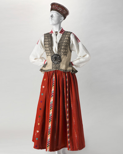 Mannequin dressed in a Latvian black silk bonnet with a drawstring cord at the neck, a red ankle-length skirt, a white linen shirt and a waistcoat decorated with an embroidered black pattern of geometric curves.