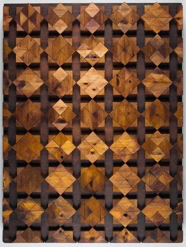 Three-dimensional rectangular artwork in portrait orientation. The artwork's surface is made up of many triangular pieces of pinewood assembled into a grid of eight-pointed star shapes. The triangular pieces of pinewood are various shades of yellow-gold, golden-brown and brown. The star-shapes sit in relief on a dark-coloured base, or backboard of plywood.