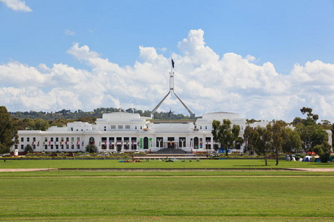 Photo showing white exterior of a buildling, with a line of flags and grassed area at the front, and the flagpole of new Parliament House behind.