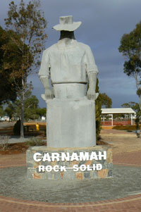 Sculpture depicting a farmer with a sack of grain. 'Carnamah, Rock Solid' is written on the base