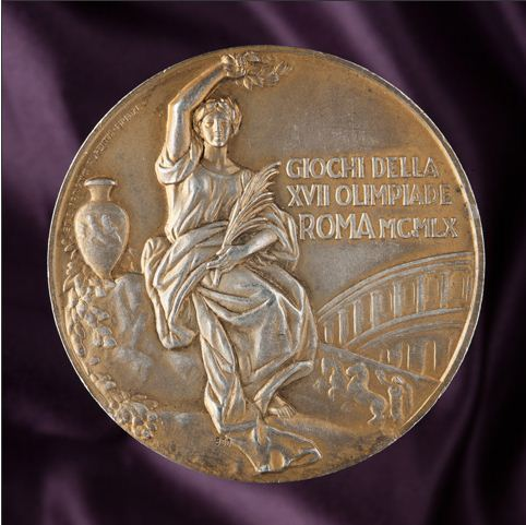 Yellow-coloured circular medal with a classical image showing a woman dressed in a robe, sitting cradling a small branch in her right arm and holding a laurel above her head with her left. An urn apears to her left and part of an arched bridge to her right. The medal has been inscribed with the text 'GIOCHI DELLA / XVII OLIMPIADE / ROMA MCMLX'