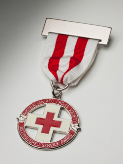 A Red Cross badge hanging from a silver bar and a ribbon with vertical white and red stripes. The circular award features a central red on cross on silver background, with the words 'AUSTRALIAN RED CROSS SOCIETY / DISTINGUISHED SERVICE AWARD' on an outer circle.