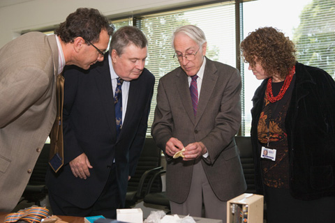 Two men and one woman leaning in to look at a small bone being held by Graeme Clark.