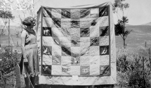 Black and white photo of a young woman with a large quilt. A rural landscape forms the backdrop.
