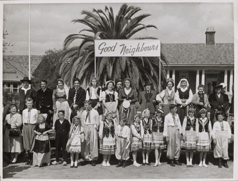 Black and white photograph of a group of adults and children standing in two rows, wearing various traditional national costumes. The group stands beneath a 'Good Neighbours' sign and in front of a palm tree and building.