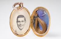 Detail of an open locket revealing a photo of a man on one side and a lock of hair on the other