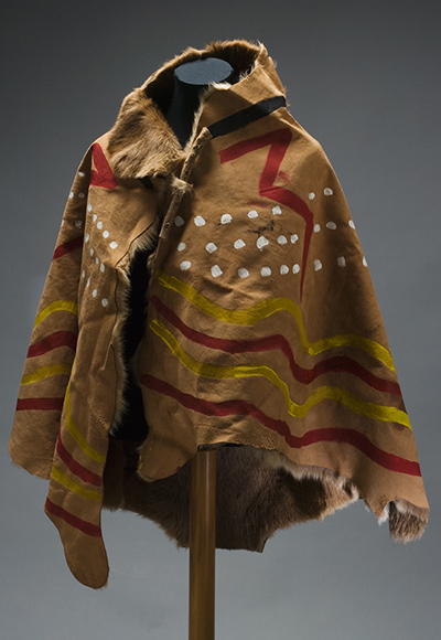 Front view of the booka, with fur on the inside, showing the painted designs using the colours red, yellow, white and black.