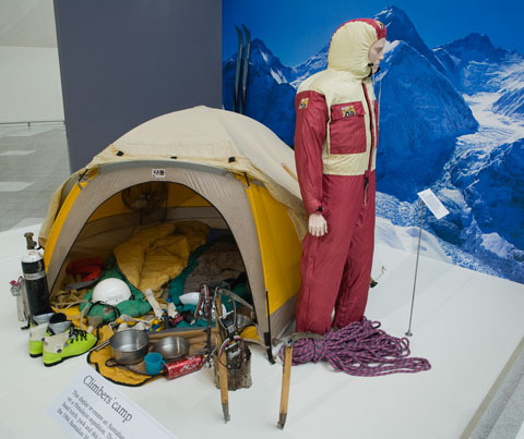 An open tent with camping and mountaineering gear inside and at the front, with a mannequin in a maroon and yellow windsuit at right. An image of snow-covered mountains forms a backdrop.