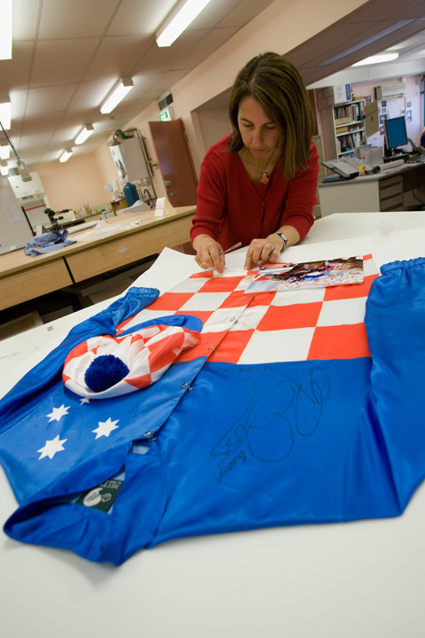 Conservator Carmela Mollica working on Makybe Diva jockey silks worn by Glen Boss. They were commercially framed using staples and double-sided tape to attach them to the backing board. This provided a challenge to conservators.