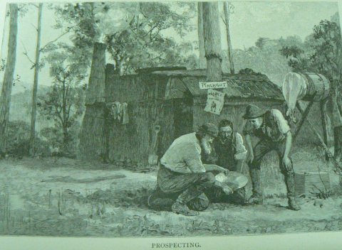 Three miners outside a shack peering at a gold pan.