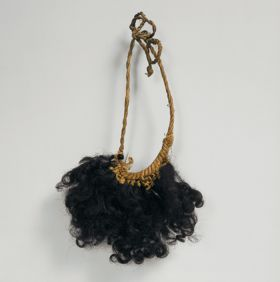 Arm or leg ornament made of the locks of curled human hair wrapped with fibres and set into a plaited band.