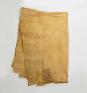 A piece of thin barkcloth dyed a yellow-brownish colour that also exhibits some reddish and greyish discolouration. Used as a cloak-like cape.