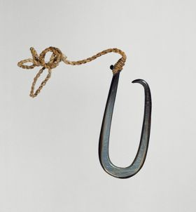Fishhook made of a large dark purple pinna shell where strings made of various plant fibres are attached.