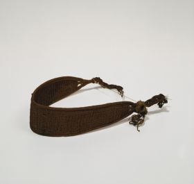 Headband made of plaited plant fibre that tapers towards the two ends with several plaited strings to fasten it.