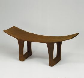 Headrest made of a piece of brown wood with a broad top that is hollowed in and four legs, linked by a crossbar of about the same thickness as the legs.