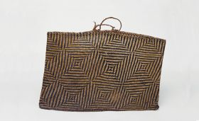 Basket made of light and dark brown flax strips plaited together in a geometric pattern, with handles made of twisted cord.