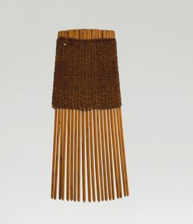 A comb made of twenty small sticks held together by a weave of red-brown and dark brown strings at the grip end.