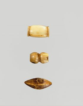 Three bone ornaments. The first is barrel-shaped, the second is a round long piece grooved around the middle, and the third is in the shape of a boat or roof.