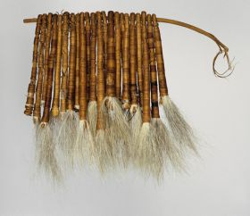 Tufts of dog hair bundled together into twenty-two tassels and tightly wrapped both length-wise and crosswise with fine coconut fibre threads and threaded onto a stick.