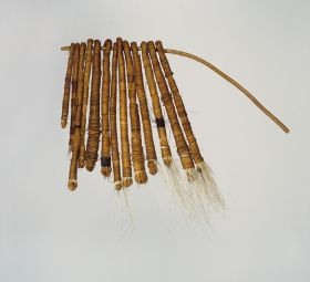 Tufts of dog hair bundled together into thirteen tassels and tightly wrapped both length-wise and crosswise with fine coconut fibre threads and threaded onto a stick.