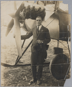 A black and white photo of a man standing at the front of plane, with one hand resting on a propeller blade.
