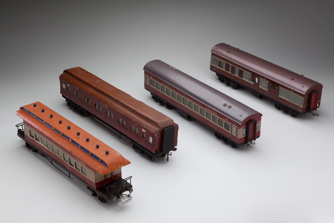 (l-r) New South Wales Railways air-conditioned saloon car (SBS); Victorian Railways country passenger car; New South Wales Railways air-conditioned passenger coach (SFS); and New South Wales Railways guard/power van. Each made with pressed metal rooves, wooden chassis and die-cast bogie components, by Frank Slovnic