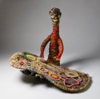 A sculpture depicting a person working on a painting. The sculpture is made of woven grass, plant material dyed in different colours and strands of wool.