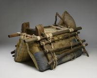 A camel packsaddle with a wooden frame secured with ropes. The wooden frame surrounds padded hessian and cloth bags.