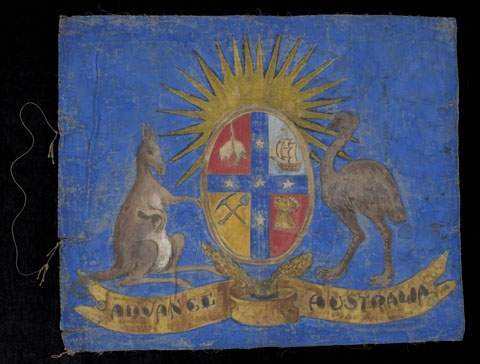 A hand-painted flag depicting a kangaroo and emu on either side of a shield, against a bright blue background. The shield is broken into four sections showing a sheep, a sailing ship, a sheaf of wheat and a pick and shovel. The stars of the Southern Cross separate the quadrants and a rising sun appears above the shield. A banner below the coat of arms reads 'ADVANCE AUSTRALIA'. At the left edge a hoist cord stitched at two points to the flag.