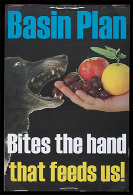 Colour photograph of a poster on a black background, with a central image of a dog biting an extended hand holding fruit. Printed text reads: 'Basin Plan. Bites the hand that feeds us!'