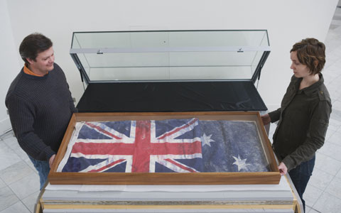 Two Museum staff members moving an Australian flag, retrieved from the ruins of the World Trade Center, into a display case.