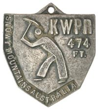 An image of a worker holding a tool above his head and in a digging stance is in the centre of the medal. 'KWPR 474 FT' is written in the top right corner and 'Snowy Mountains Australia' is written down the left hand side.
