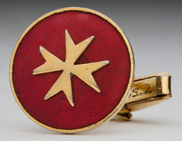 Gold cufflink with gold Maltese cross on red background