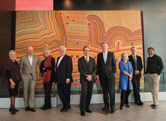 Council members standing in front of a large Aboriginal painting, from left: Barbara Piscitelli AM, Nicholas Davie, Andrea Hull AO, John Morse AM, Andrew Sayers AM, Daniel Gilbert AM, Rae Francis, David Jones, Peter Yu.