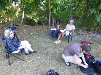 A group of people sitting in portable chairs in a shaded, grassed area. A video camera on tripod can be seen in the background.