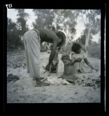 A black and white photographic negative that depicts an Aboriginal man wearing a hat bending over next to a child with a woman and dog sitting in the background.
