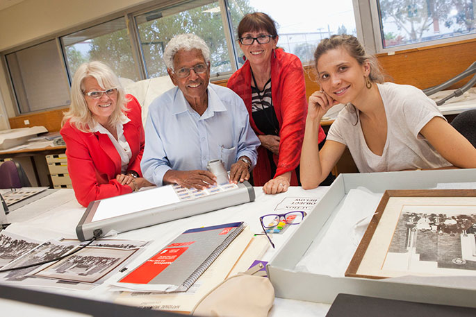 A man and three women standing at a bench, with photos and a lightbox on the benchtop.