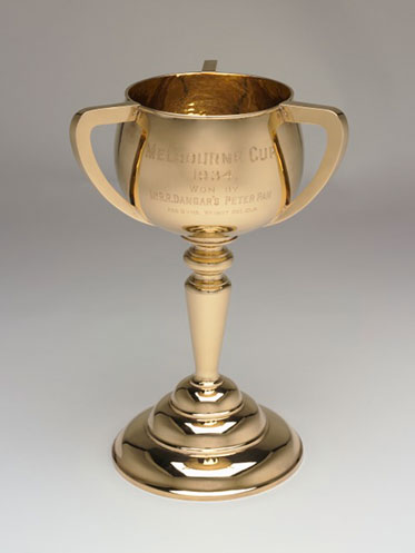 Three-handled gold cup engraved with 'MELBOURNE CUP, 1934, won by Mr RR Dangar's Peter Pan, age 5 yrs. Weight 8st 10lb'.