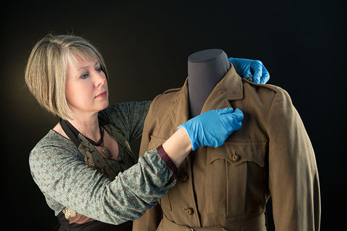 Conservator Michelle Newton-Edwards working on a woollen jacket worn by a member of the Australian Women's Army Service.
