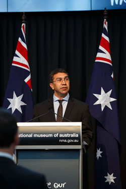 A man at a lecturn. The Australian flag is displayed in the background