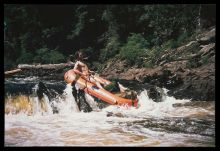 A man in a raft leans back as he negotiates the rapids in a river.