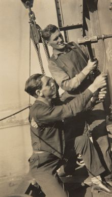 Two men work to drive a metal pin into a section of bridge.