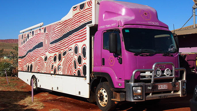 A large purple truck with Indigenous artwork on its side.
