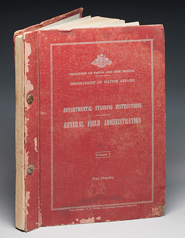A red hardcover book with a loose leaf inside the front cover. The book features two gold coloured fixings through spine, and silver coloured text on the front cover, which is within a silver border and reads 'TERRITORY OF PAPUA AND NEW GUINEA / DEPARTMENT OF NATIVE AFFAIRS / DEPARTMENTAL STANDING INSTRUCTIONS / GENERAL FIELD ADMINISTRATION / Volume 1 / Port Morseby'.