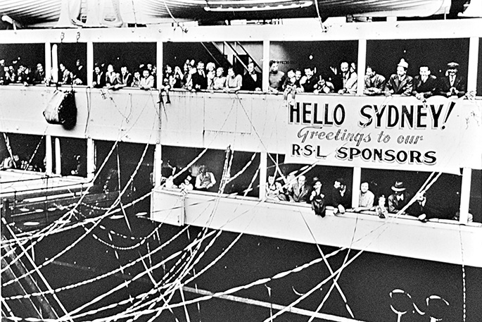 Ship docking with streamers strewn between ship and shore. A banner on the ship reads 'Hello Sydney!'