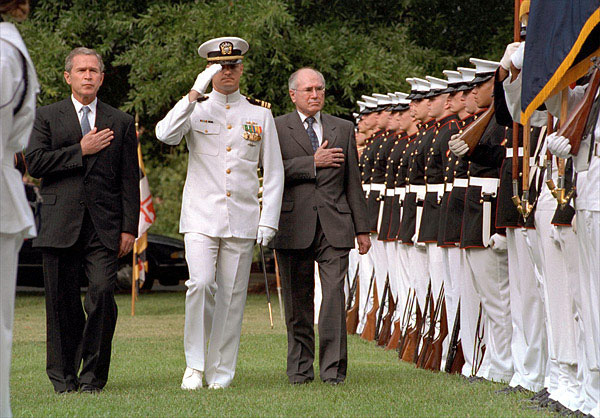 President Bush and Prime Minister Howard walking with hands on hearts on either side of a US Navy officer. A line of marines in full-dress uniform stand to attention on their left.