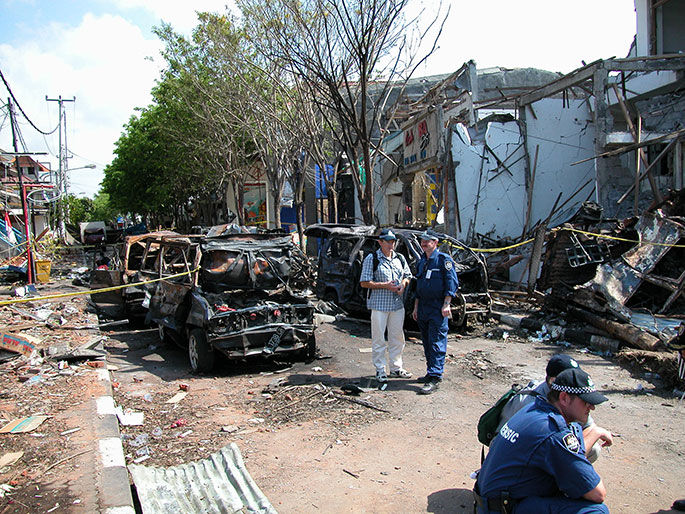 Four AFP officers, two in uniform, confer in the street. Behind them are the burnt-out remains of vehicles and a wrecked building