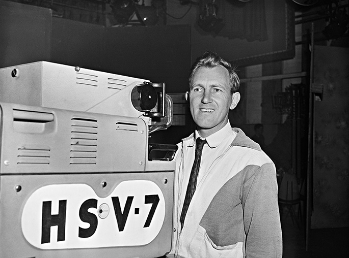 smiling camera man behind large camera with HSV 7 marked on the side. Taken inside a TV studio.