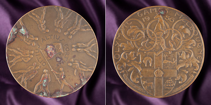 The front and back of Konrads 1956 Olympics participation medal.
