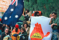 Young people squatting or standing on a dirt road holding the Australian flag and various banners.